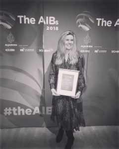 I'm holding a certificate and smiling happily after winning an award at the Association for International Broadcasters. The CNN team who had cleaned up with prizes took my photo